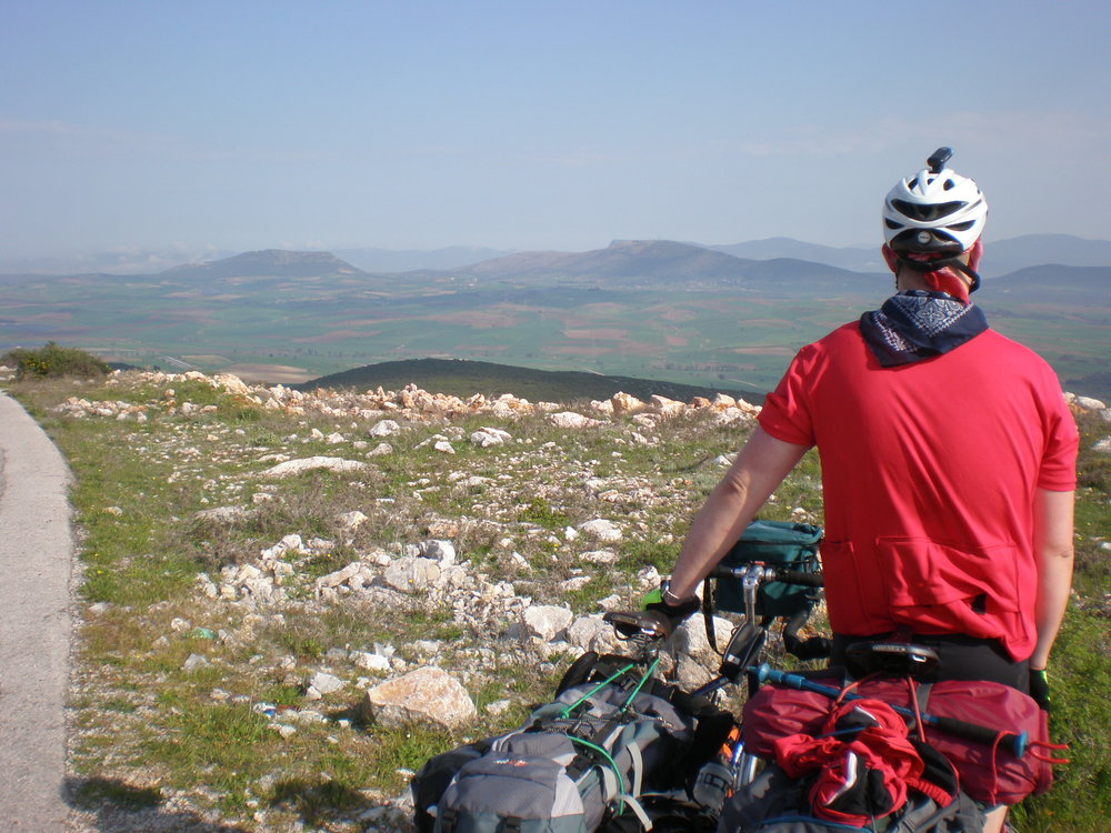 Here he is staring out at the Greek countryside with his bike.