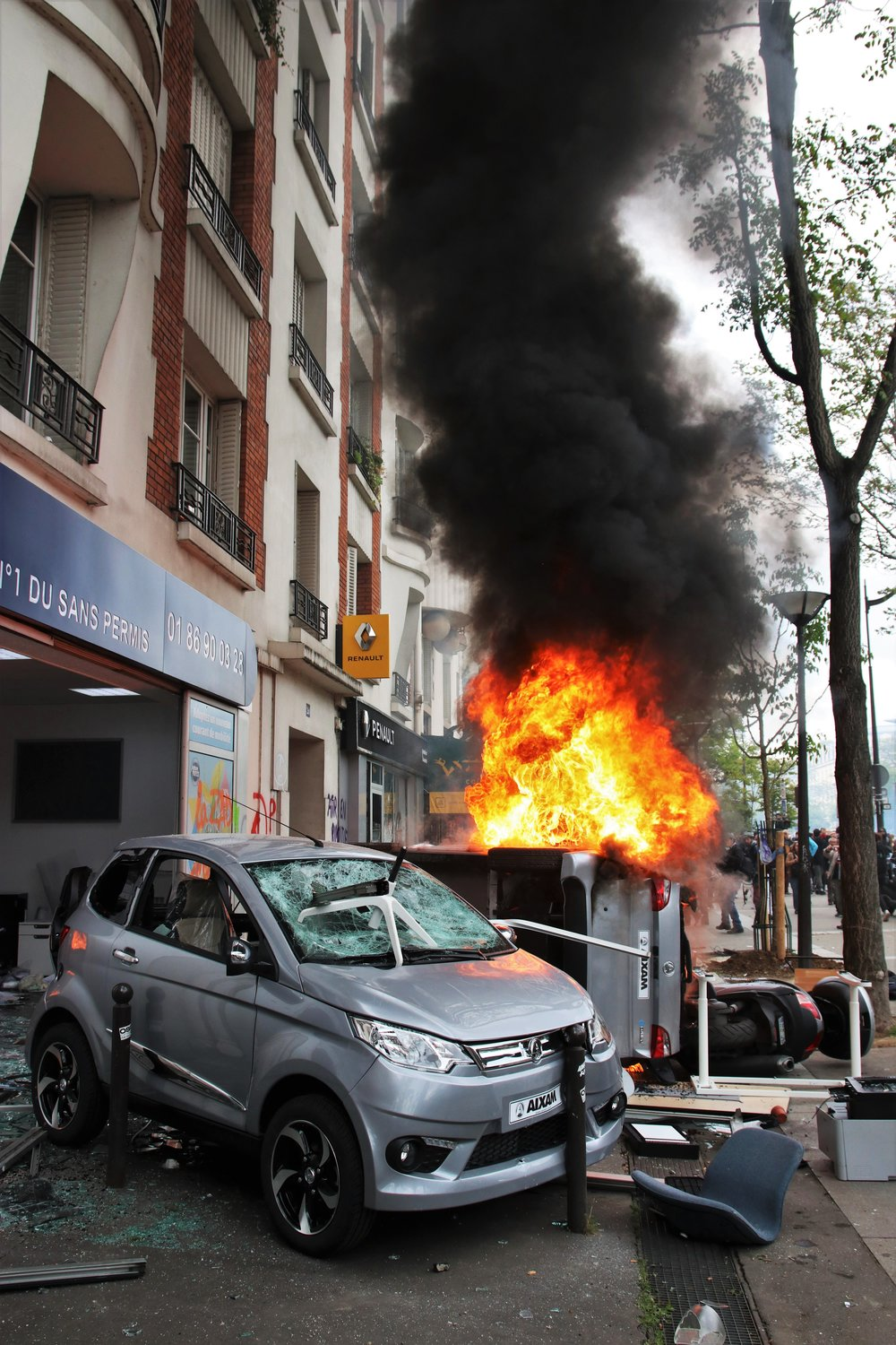 The contents of a car showroom are dragged into the street and burnt during May Day demonstrations in Paris