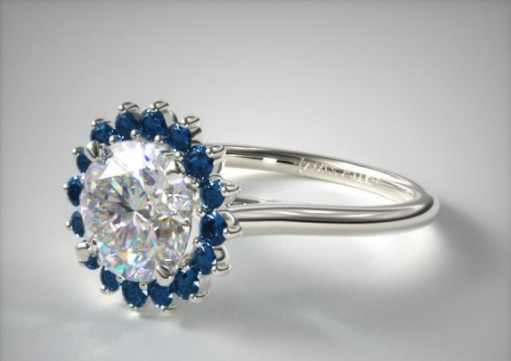 Halo:  In a Halo setting a central solitaire is surrounded by one or multiple rows of diamonds and/or precious gems. This setting can help make a smaller solitaire appear larger, or accentuate a lower Color grade solitaire by surrounding it with 1 or 2 grade lower halo diamonds. In the example above this James Allen Halo surrounds the solitaire with Blue Sapphires.