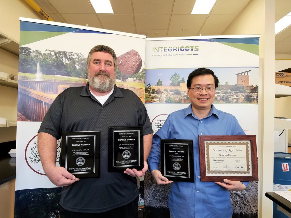 Integricote CEO, Prof. Shay Curran (left) and CTO, Dr. Shawn Liao (right) holding the patent awards.