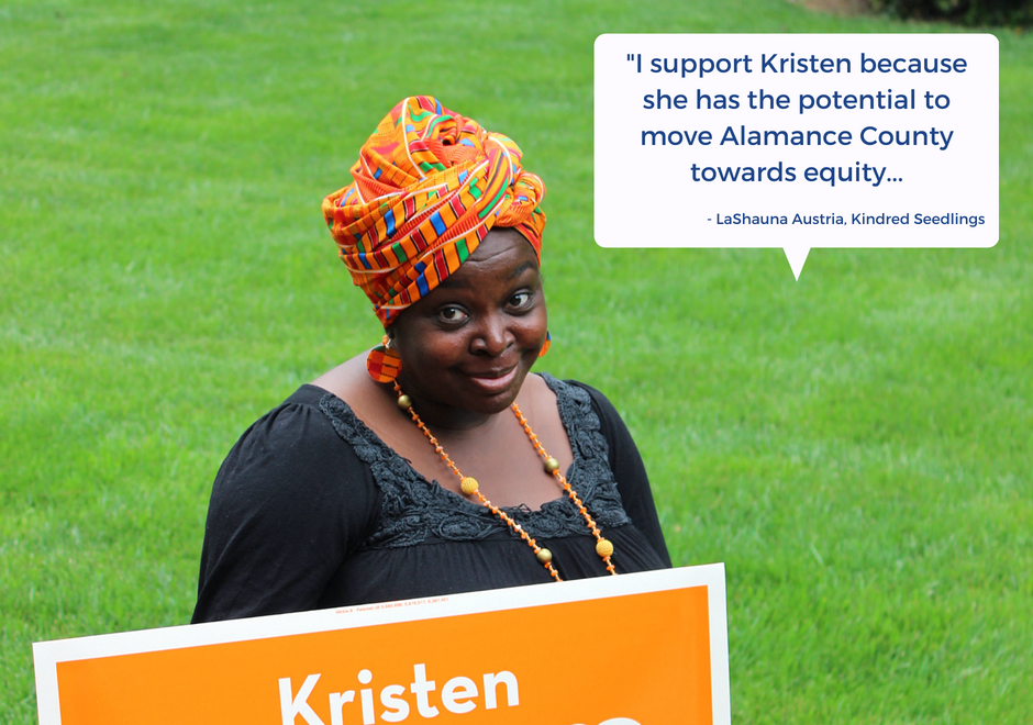 Caption: LaShauna Austria stands holding a Kristen Powers yard sign.