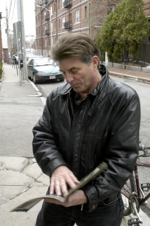 Poet Populist Peter Payack can often be spotted wearing a black leather jacket as he zips down Mass Ave on bike. (Photo Credit: Terrell Woods)