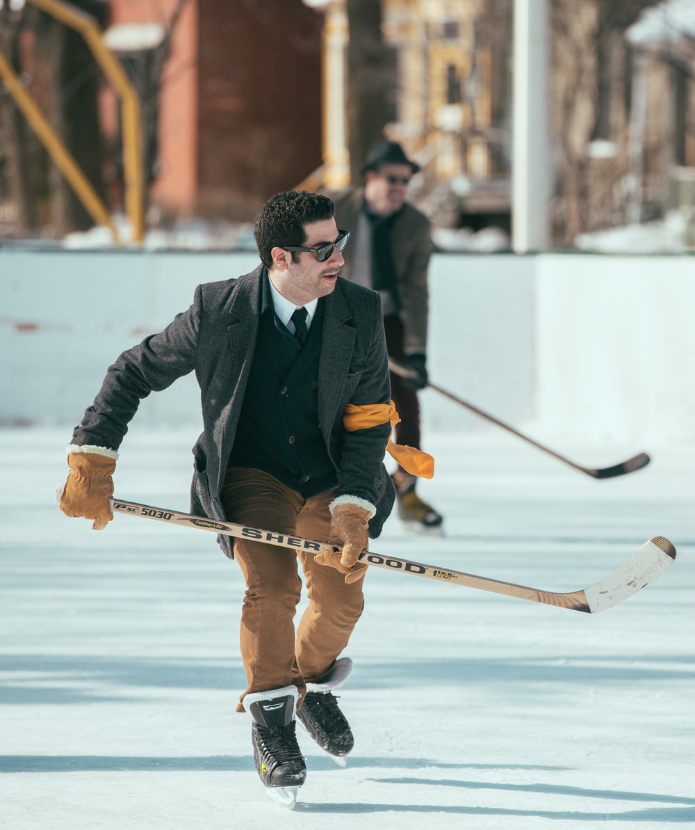 """Origins - The WRG Classic was born with blazers and bow-ties, tweeds, prints and of course personal flare. Both men and women adorn these early 20th century fashions.The national pastime and pride of Canadians both home and abroad, the sport of hockey is in our DNA.Throughout the 1920s and 1930s, men could be found wearing suits to the rink, both on and off the ice. While the Classic does not have a strict dress code, both players and fans are encouraged to attend in """"rink casual dress"""" which amounts to business casual with some winterized flare."""