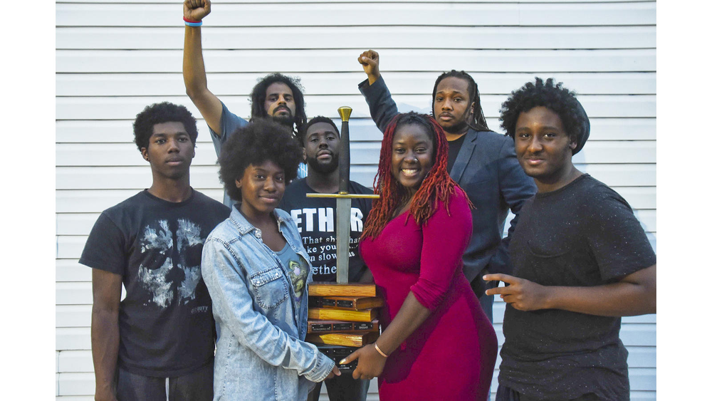 "(Clockwise from left) Members of the youth and adult slam teams ""Grim"" Jackson, Slangston Hughes, Black Chakra, Kenneth Morrison, Deniero Black, Lady Brion, and MeccaMorphosis hold up the National Poetry Slam trophy.    (J.M. Giordano/City Paper)"