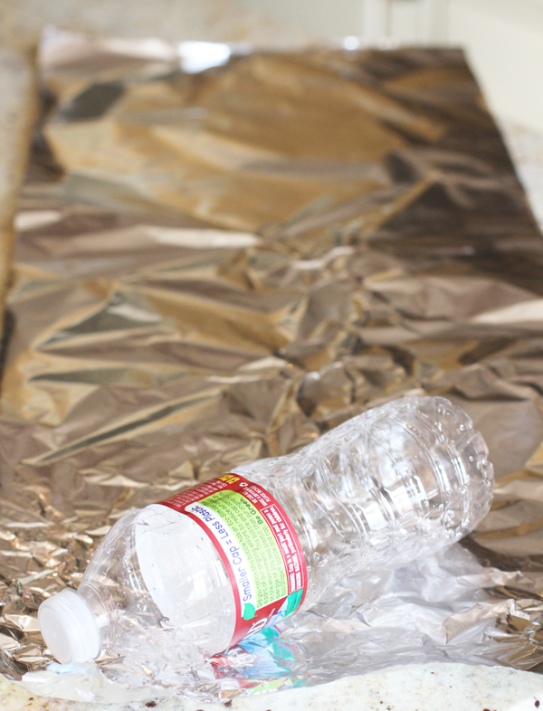 """To start the cornucopia you first need to create your mold so depending on the size of your cornucopia you want to use a regular sized water bottle (for a 10-12"""" Cornucopia) or an extra large water bottle (for a 16-18"""") Cornucopia. If you have crafting paper this is even better. Make a paper cone and use that as your mold. Lay out a sheet of foil and start wrapping your water bottle or paper cone at an angle."""