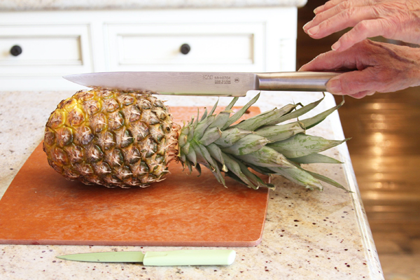 "Now lay your pineapple on its side and line your knife up so it is directly in the middle of the pineapple. Now this is where Papa starts getting all crazy.  ""Jessie, make sure your knife is lined up. Make sure the knife is exactly in the middle of the pineapple. If it's on the side you're going to screw it all up Jessie. Make sure the knife is lined up, do you hear me? Check the knife again. Is it lined up?""  ""Yes, I hear you Papa. Position the knife to the side so everything goes crooked and I almost cut my finger off."" Jessssssssieeee!  Make sure your knife is lined up folks."