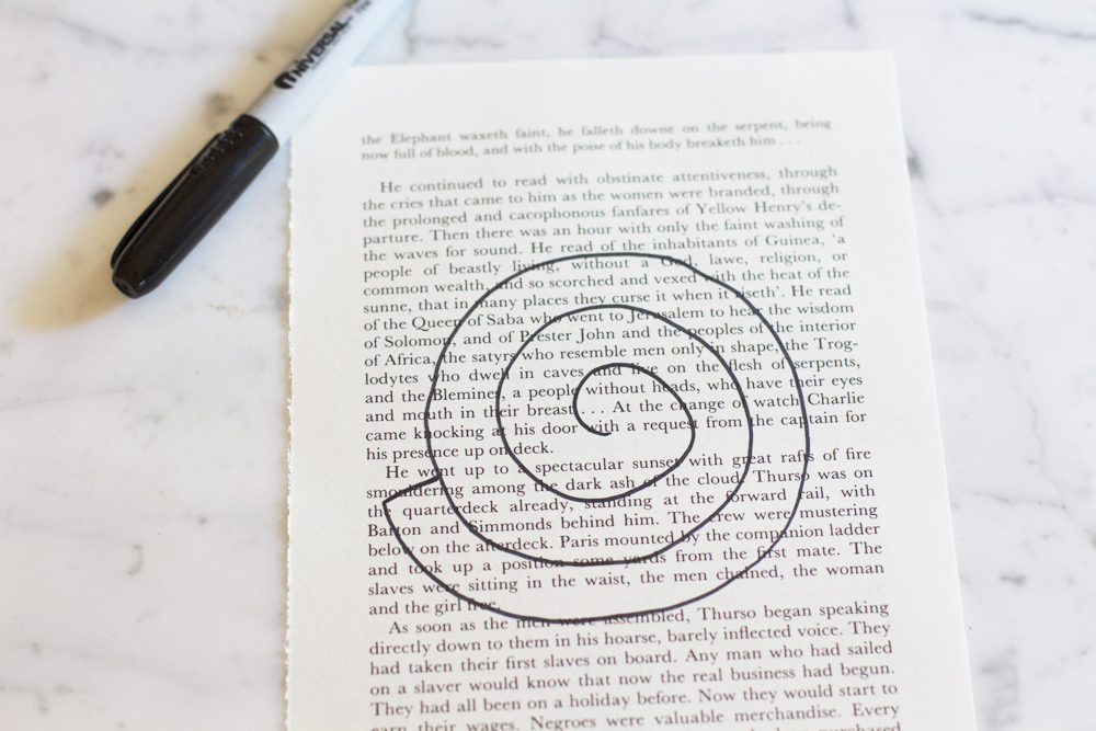 "Using a sharp blade, cut out a handful of pages of your book. Draw a 4"" x 4"" spiral on one of your book pages and close off the end. I used a sharpie in my picture above so you could see it clearly, but you should do this with a pencil so you don't have black marker showing through on every flower you make."