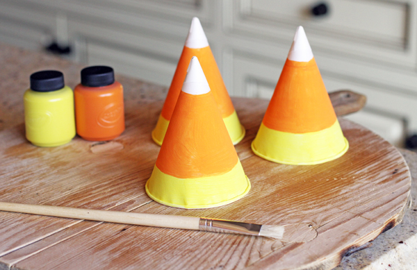 Paint your hats with orange and yellow paint. Eyeball it or use a pencil to draw a straight line around the hat - this is super simple. The white part is the actual paper cone. I did not use white paint. Let your little hats dry.
