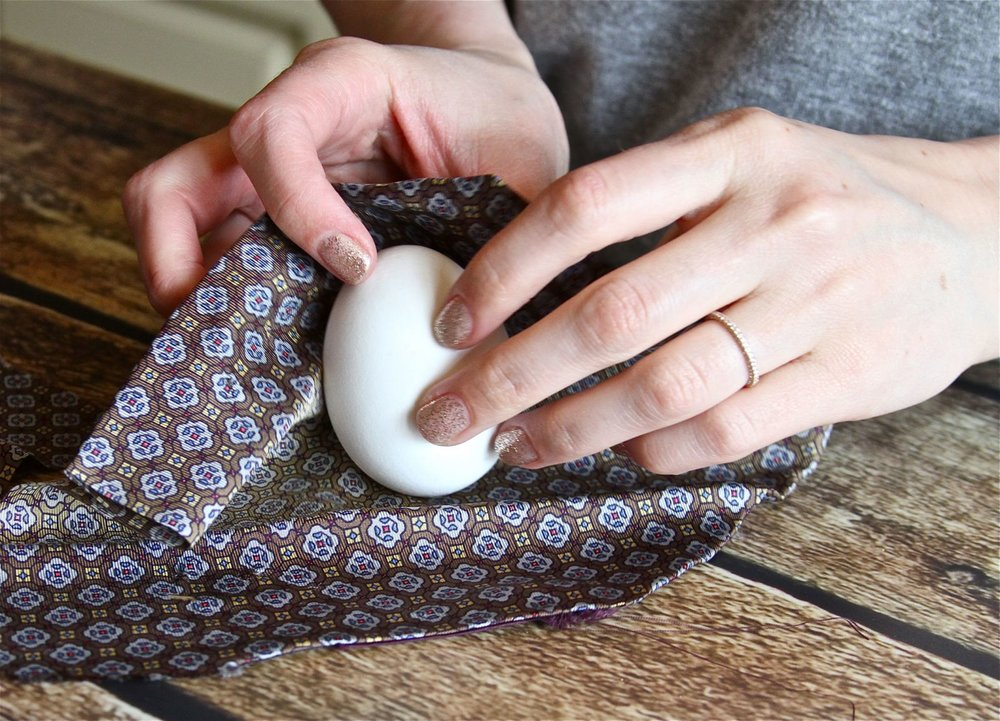 Wrap your raw egg with a piece of silk, making sure the darker printed side (the nicer side) is touching the egg. (The lighter side is on the outside) It's OK if there are wrinkles.