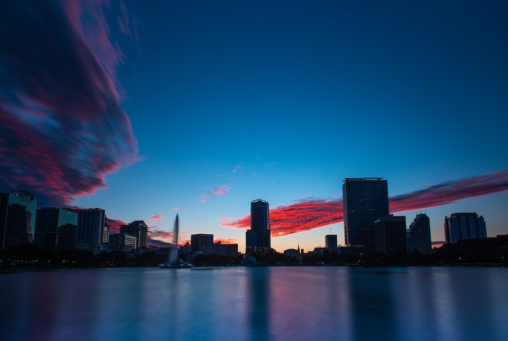 Lake Eola Sunset - This was taken on a hot summer night while walking around the lake. There was a unique sunset that night, with the sparse clouds in the sky. The color only stayed like this for minutes, so I had to rush to capture it!
