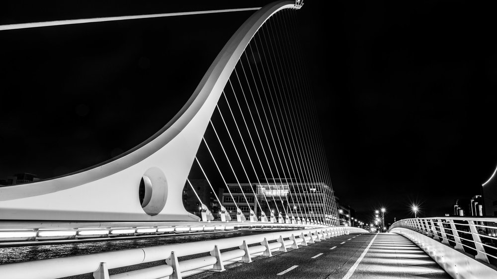 Dublin, Ireland - A black & white photo taken on a rainy night walking around Dublin. This is the Samuel Beckett Bridge, made to resemble a harp.