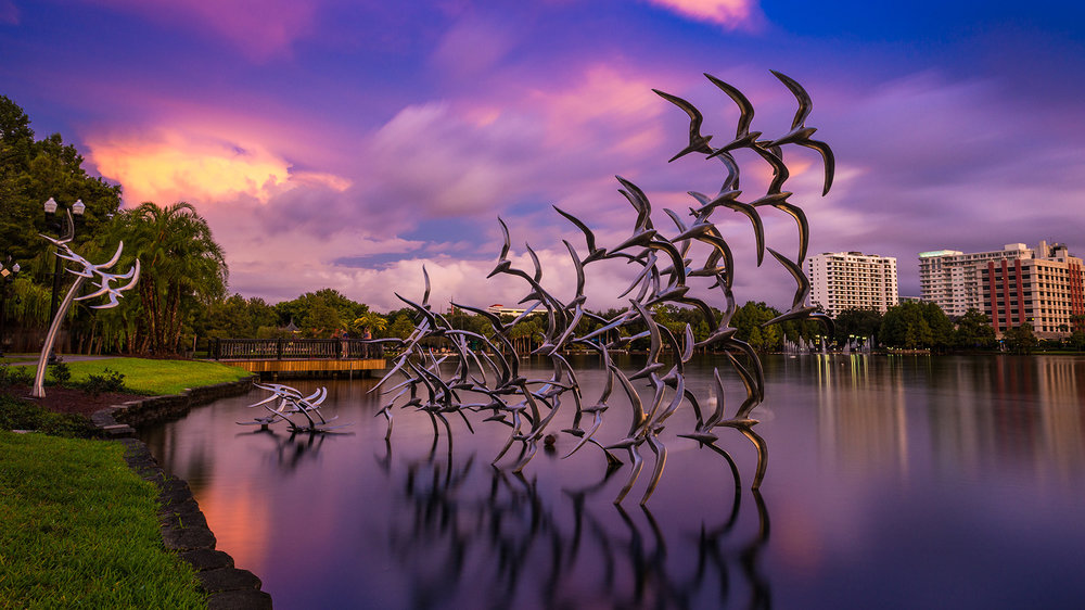 Taking Flight - I managed to catch a particularly intense sunset (the sun was setting behind me!) this day. This is a long exposure of the 'Taking Flight' scuplture at Lake Eola.