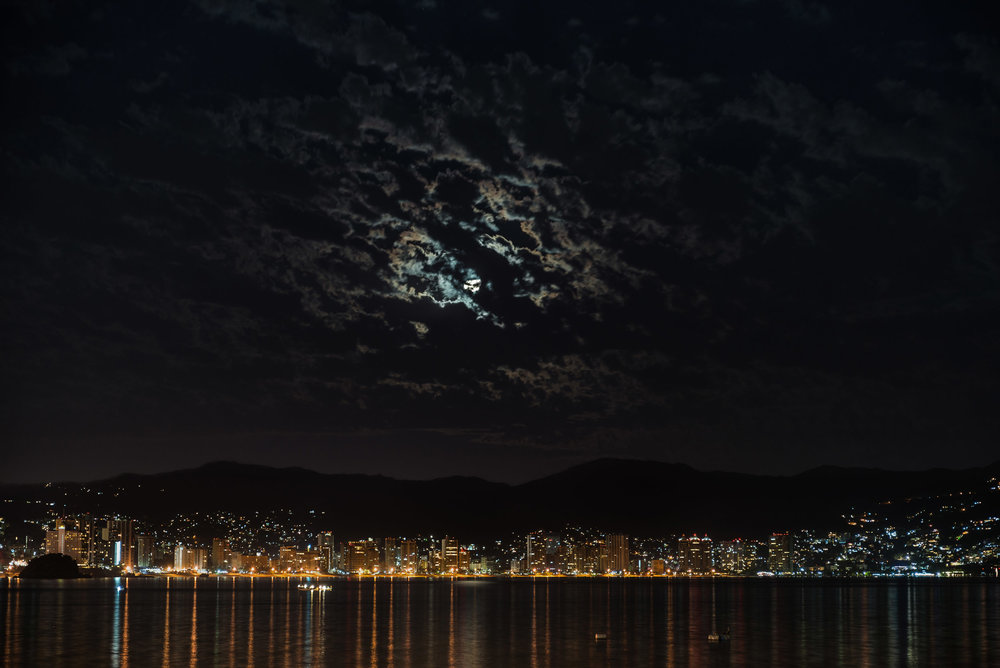 Acapulco Bay - This is a shot of Acapulco Bay, with the moon trying to peek through the cloud cover. Thanks to the moonlight, the mountains are visible behind the city lights.