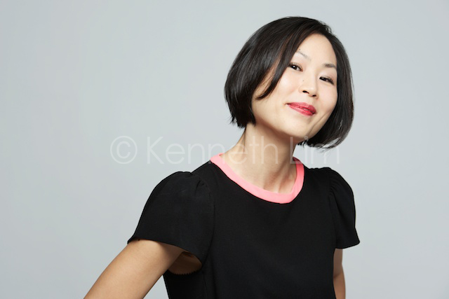 Hong Kong headshot portrait chinese woman smiling black dress gray background