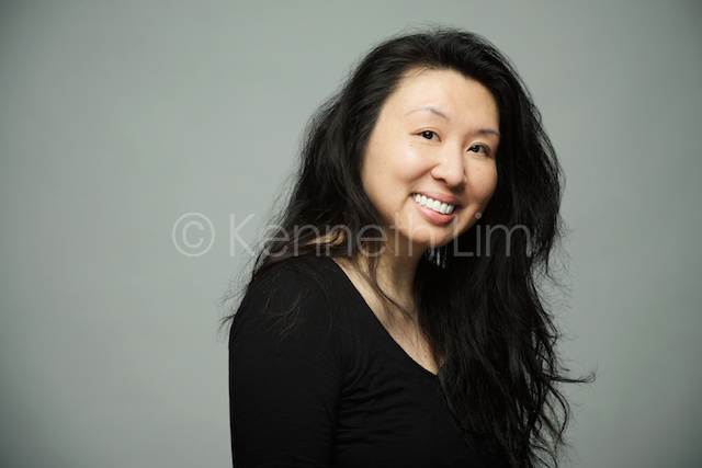 Hong Kong headshot portrait chinese woman smiling in front of gray background