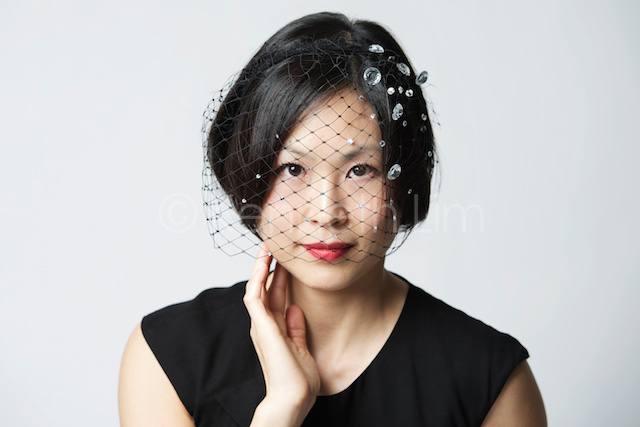 Hong Kong headshot portrait chinese woman smiling wearing veil gray background