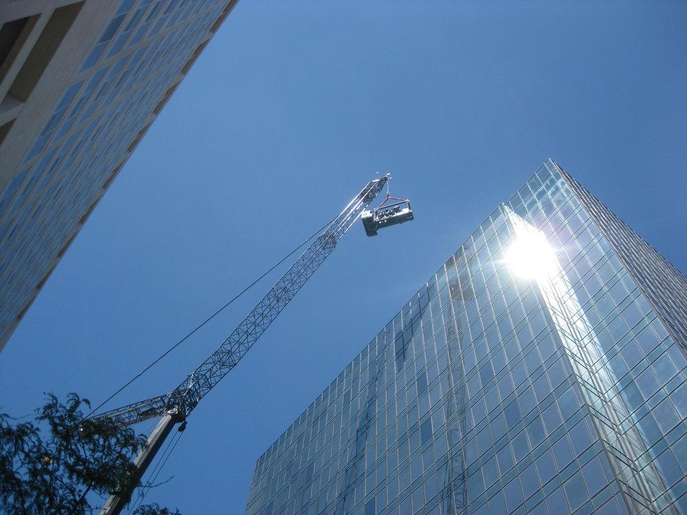 Crane installs heavy equipment on roof