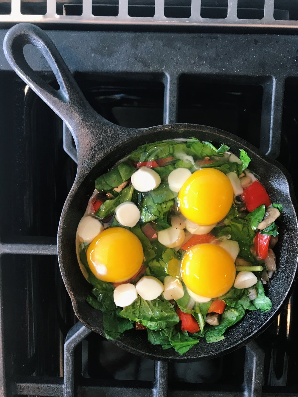 Add cheese last. Gently crack eggs over veggies then place in oven for 15 minutes, checking at 10 minutes for desired consistency.