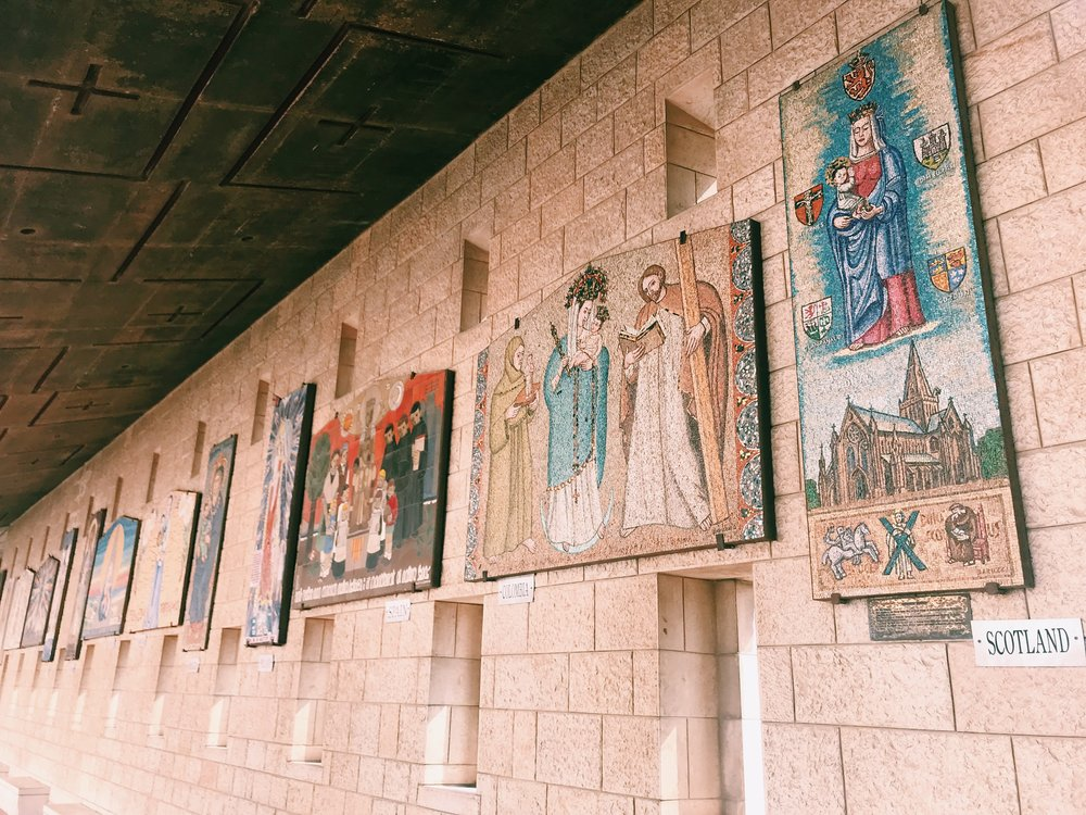 the courtyard is lined with mosaics from around the world portraying Mary and the Christ child in different cultural styles.