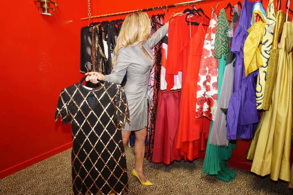 randi wood selecting dresses off a rack