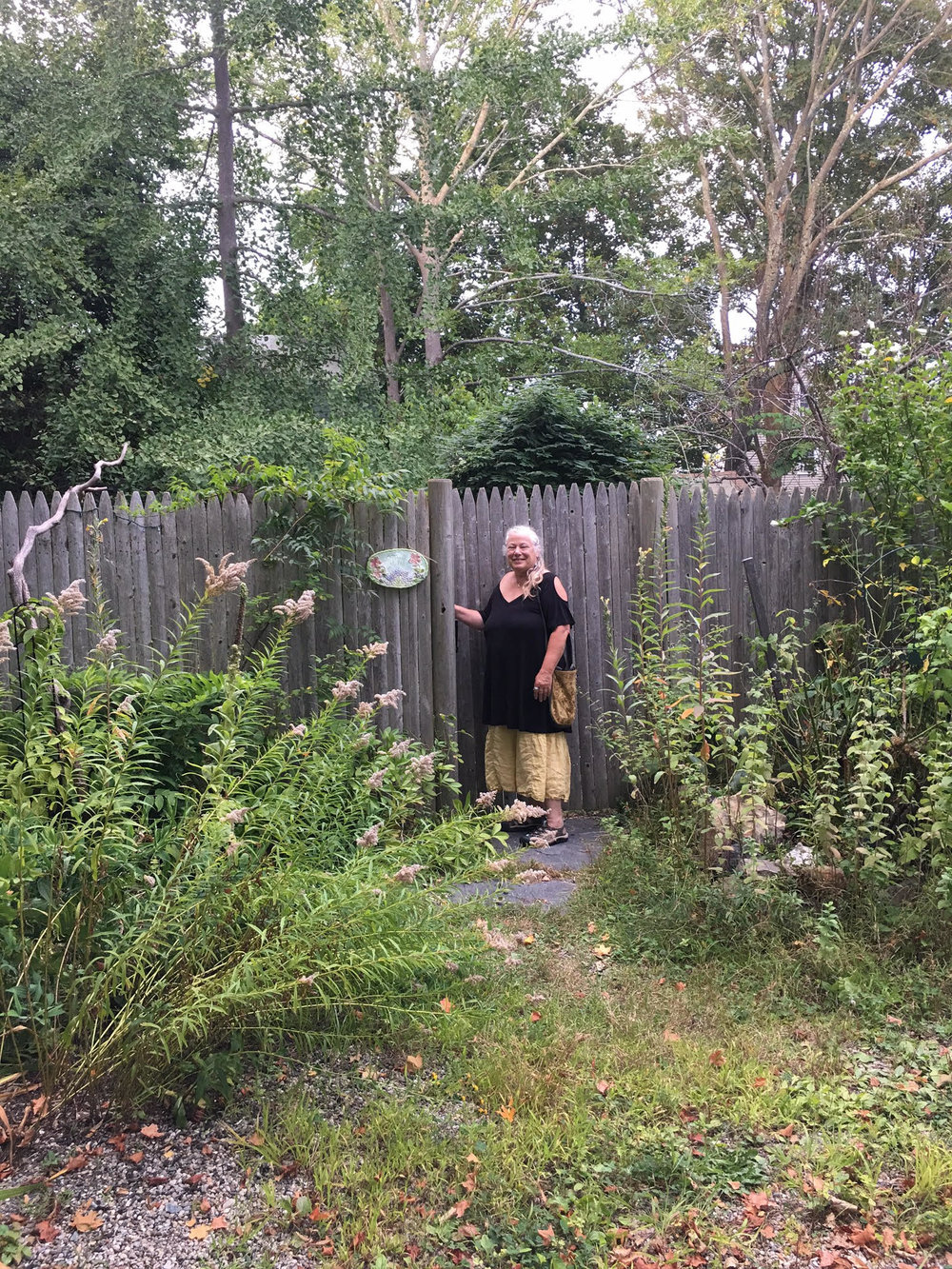 Herbalist Margi Flint stepping into her garden of medicine and beauty.