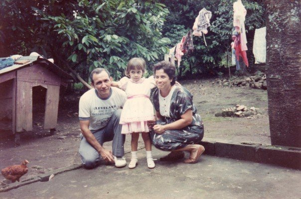 Thelma in Guatemala. IMAGE DESCRIPTION: Thelma (center) as a toddler with her mother (to the right) and her father (to the left) in her backyard in Guatemala