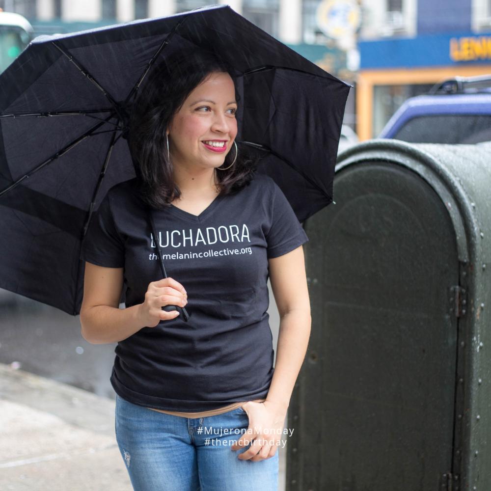 "Thelma la luchadora. IMAGE DESCRIPTION: Thelma wearing The MC's ""Luchadora"" shirt on a rainy day in NYC holding an umbrella. (URL: https://www.themelanincollective.org/store/luchadora )"