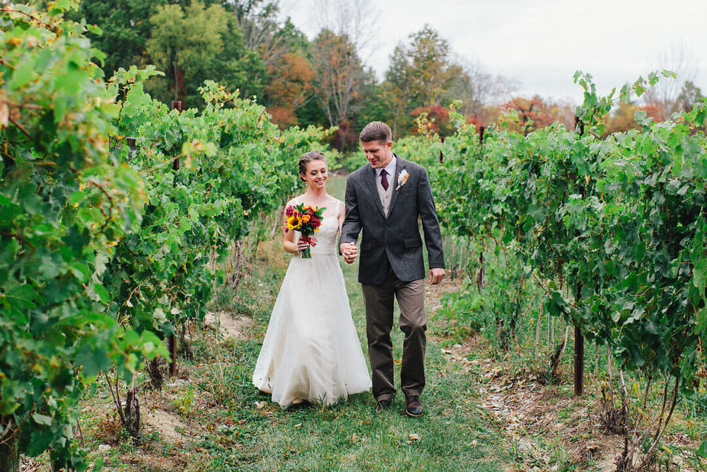 Bride and groom walking down a vineyard row in Bruynswick Vineyard.