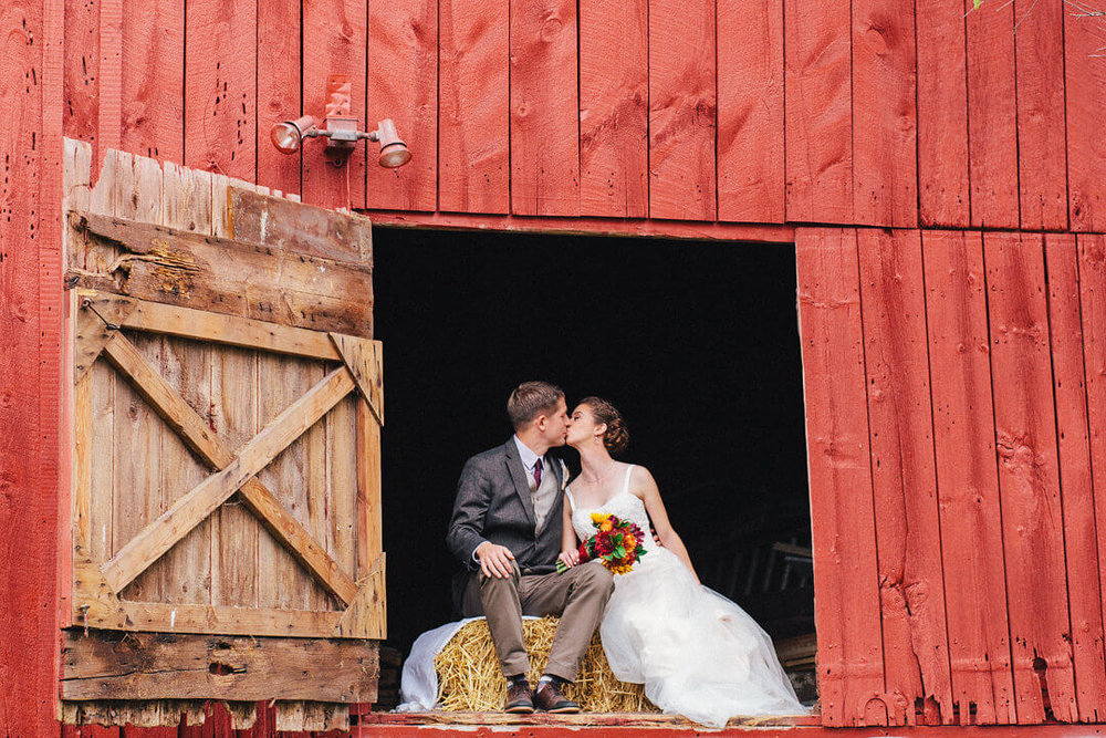 Bride and groom kissing in a red barn.