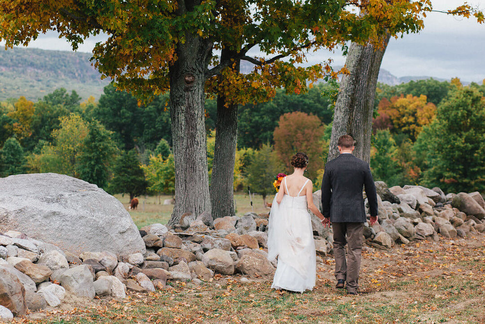 Bride and groom walking together along a rock wall.