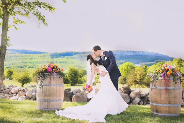 Groom holding his bride at a barn wedding in front of Shawangunk Ridge.