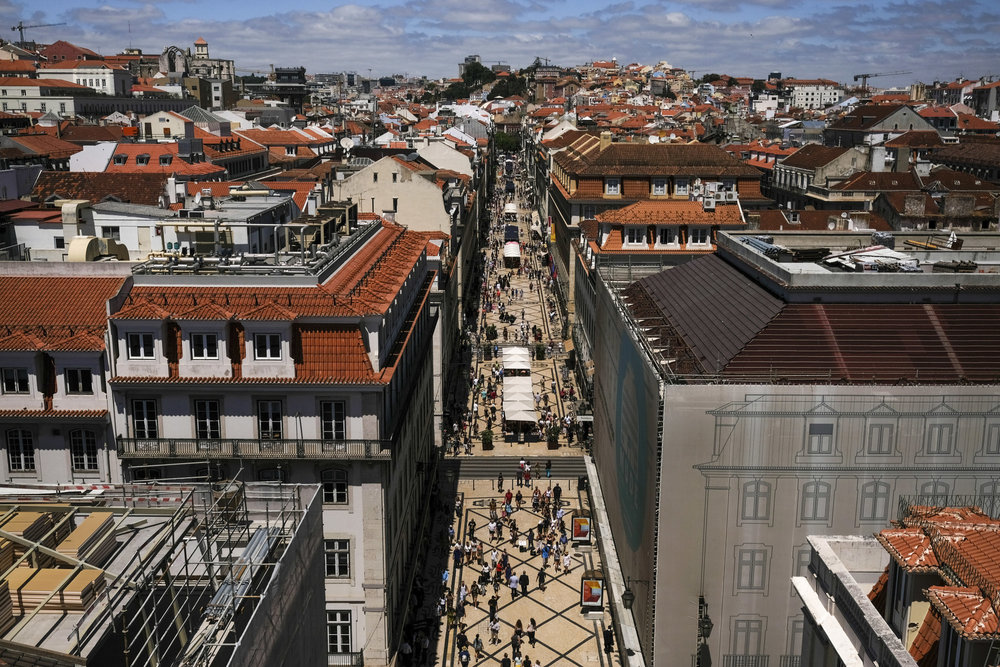 The Baixa district of Lisbon demonstrates the result of the new construction boom: renovated properties in the foreground, and 5 cranes in the distance signaling a new era of growth. (Bloomberg)