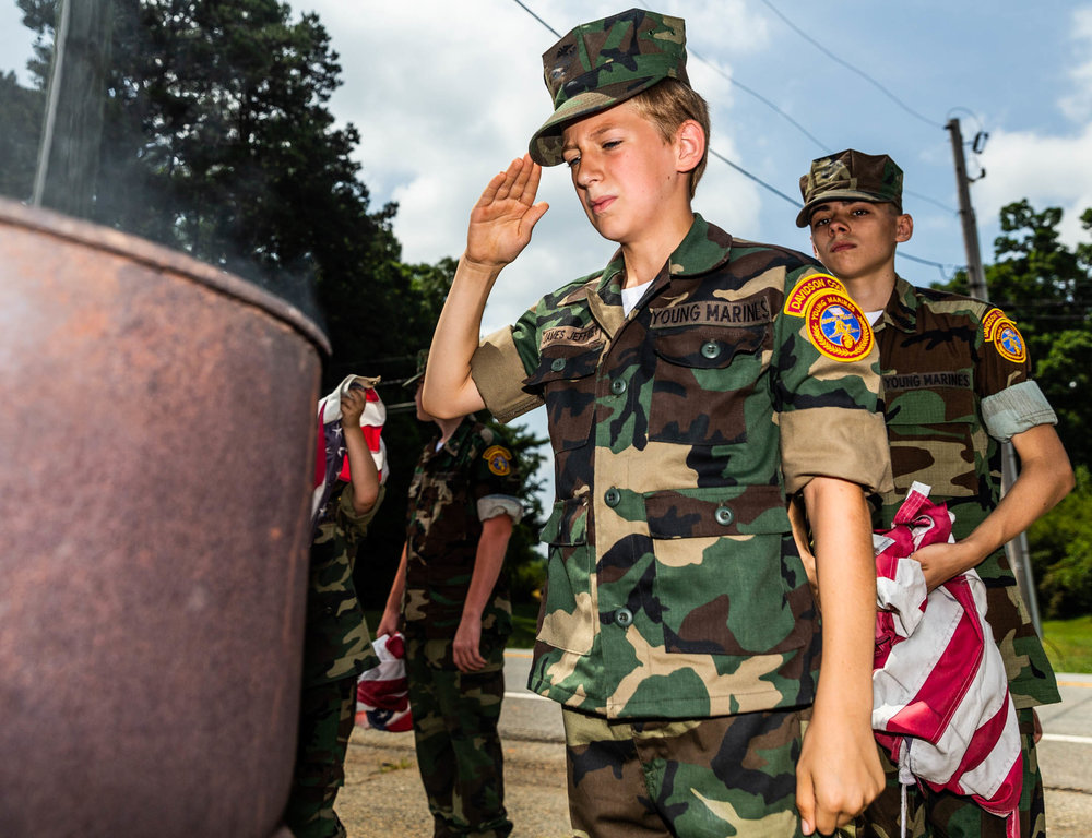 Jeffery James salutes to the flag he added to the fire barrel during a flag retirement ceremony held by the Davidson County Young Marines and the Davidson County Honor Guard on June 16, 2018 at Forest Hill Memorial Park in Lexington, North Carolina. [Dan Busey/The Dispatch]