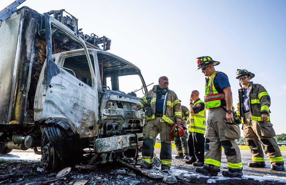 Firefighters review the cab of the box truck that caught fire August 9, 2018 on I-85 Southbound in Lexington, North Carolina. [Dan Busey/The Dispatch]
