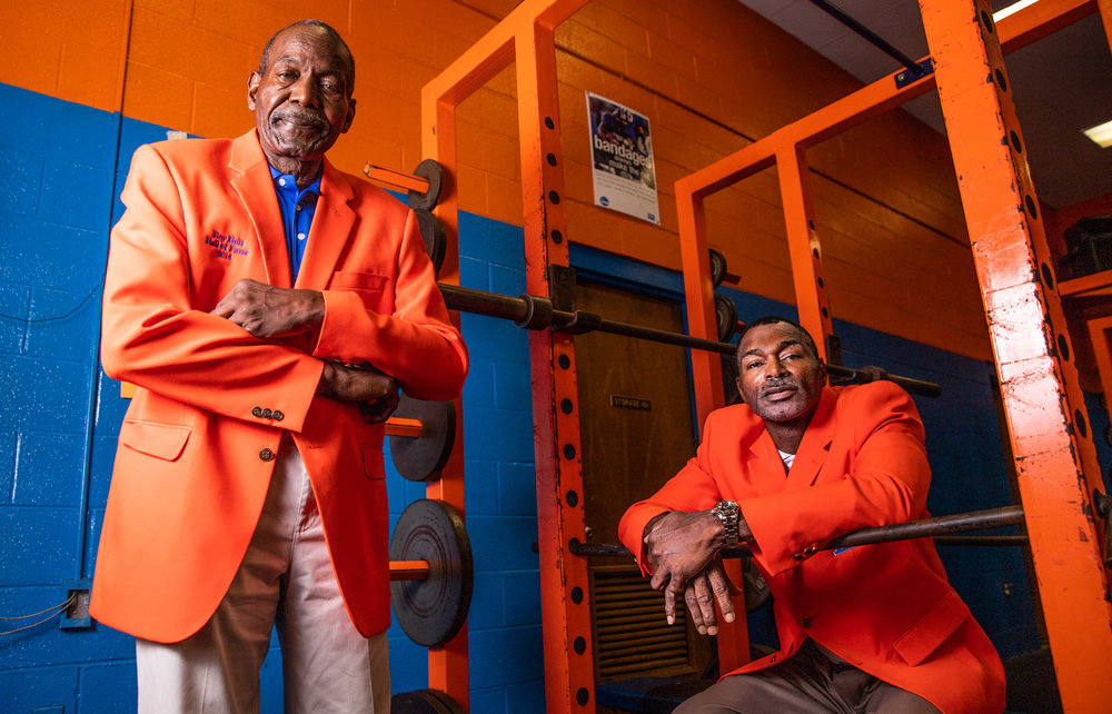 "Ron ""Tippy"" Holt, left, and Rory Holt pose for a portrait in the men's weight room at Lexington Senior High on October 1, 2018 in Lexington, North Carolina. The Holts are the first father-son duo to be inducted into the Lexington Senior High School Sports Hall of Fame. [Dan Busey/The Dispatch]"