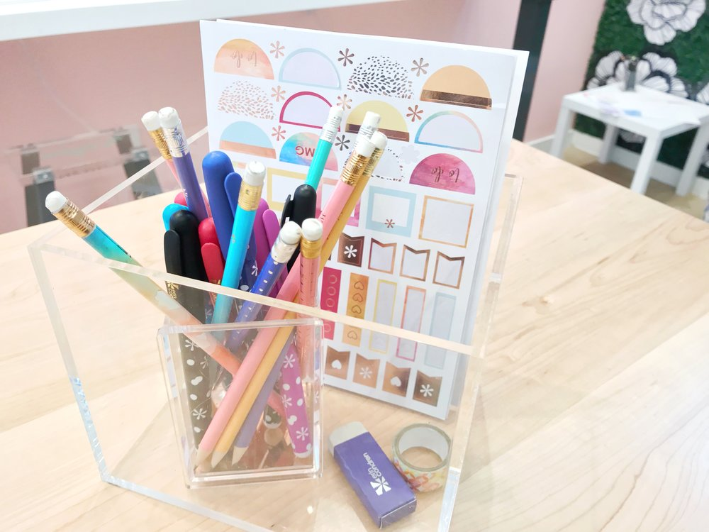 """One of my favorite areas of the store was a table with bar stools, booklets with mock-up planner pages, and acrylic boxes full of Erin Condren stickers, washi tape, and writing utensils. Before purchasing a planner, you can sit down and """"test drive"""" the different layouts with a variety of accessories sold in the store and online. What an awesome and interactive addition!"""