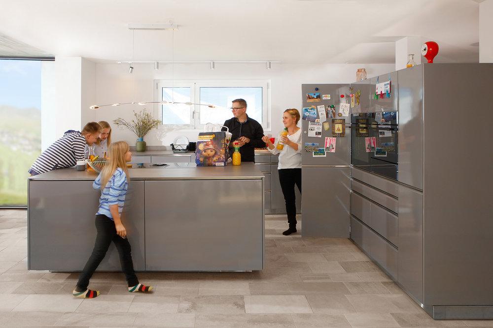 Stahlküche in staubgrau, Kochinsel mit integriertem Dampfabzug, Griffleisten in Edelstahl, Abdeckung Edelstahl 8 mm, Edelstahl Ausführung Inneschränke und Tablare.