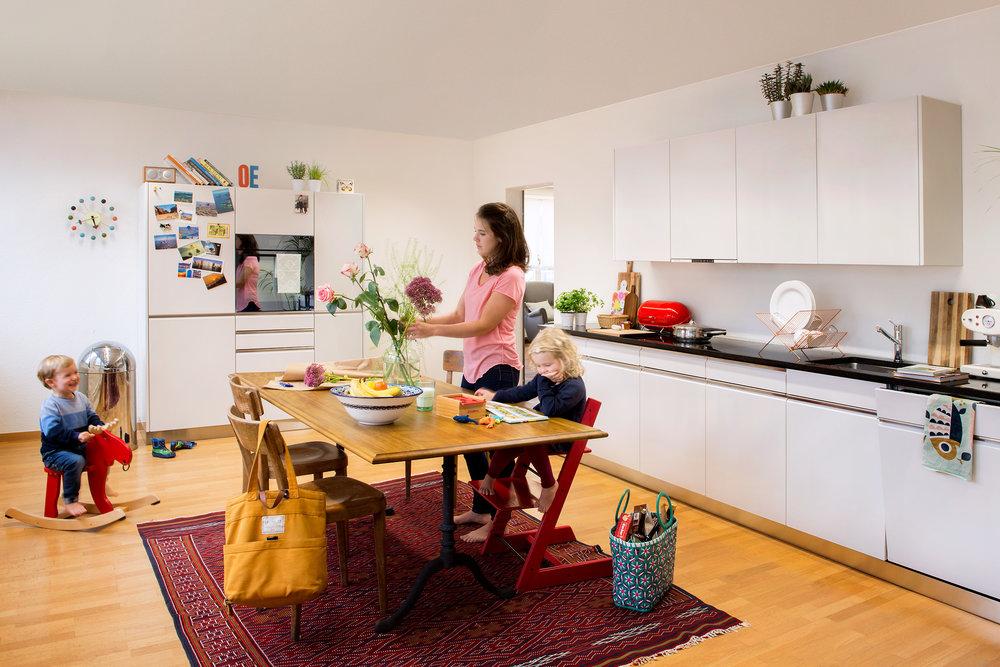 Küche in Alpinweiss, Griffleisten in Edelstahl und Nero Assoluto Steinabdeckung.