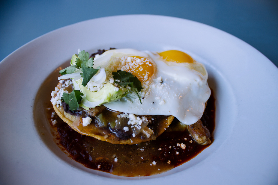 Huevos Rancheros: crispy corn tortillas, refried black beans, salsa roja, green chile stew, Cotija cheese, avocado, 2 sunny side eggs*.