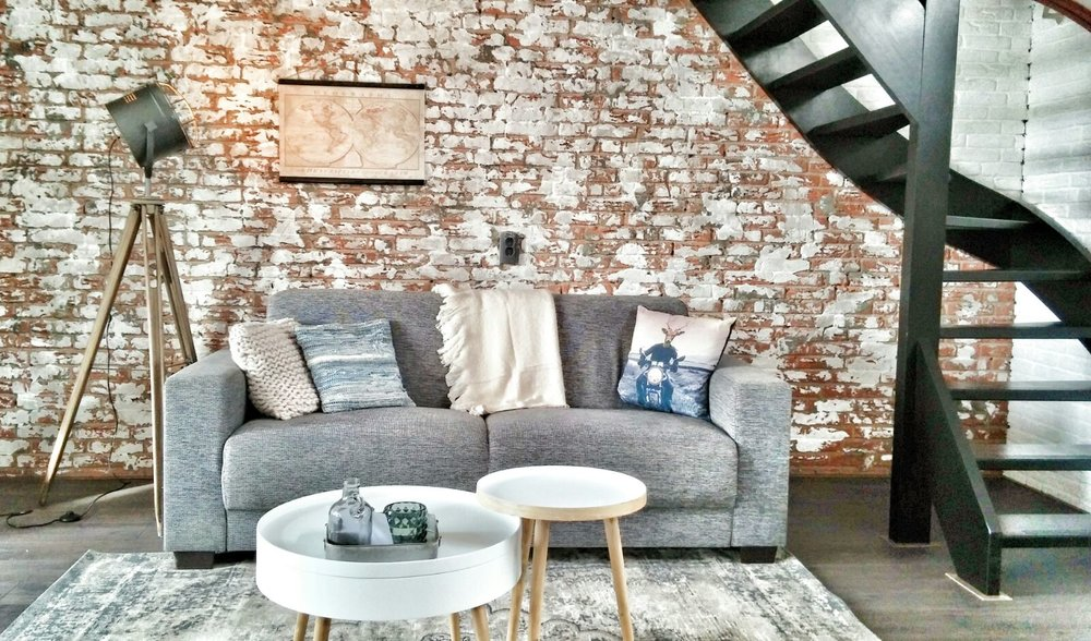 woonkamer interieurstyling industrieel brickwall bakstenen muur zwarte trap.jpg