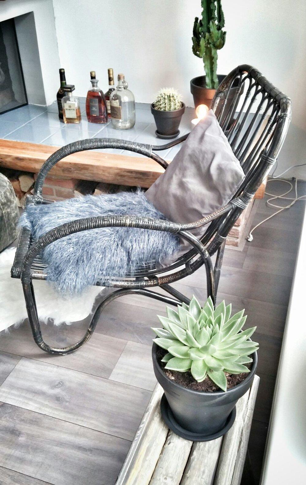 woonkamer interieurstyling industrieel stoer accessoires plant groen vacht rieten stoel schouw open haard.jpg