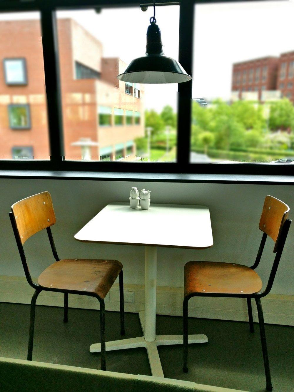 moderne kantoorruimte licht keuken eettafel industriële lamp schoolstoelen en planten.jpg