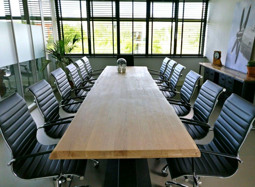 moderne kantoorruimte licht vergaderruimte vergaderzaal boomstamtafel eames chair groene planten.jpg
