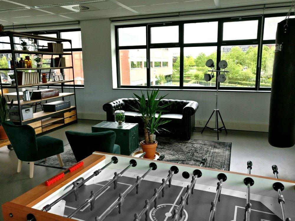 moderne kantoorruimte relaxruimte voetbaltafel oude kist chesterfield bank boxzak vintage licht n en planten.jpg