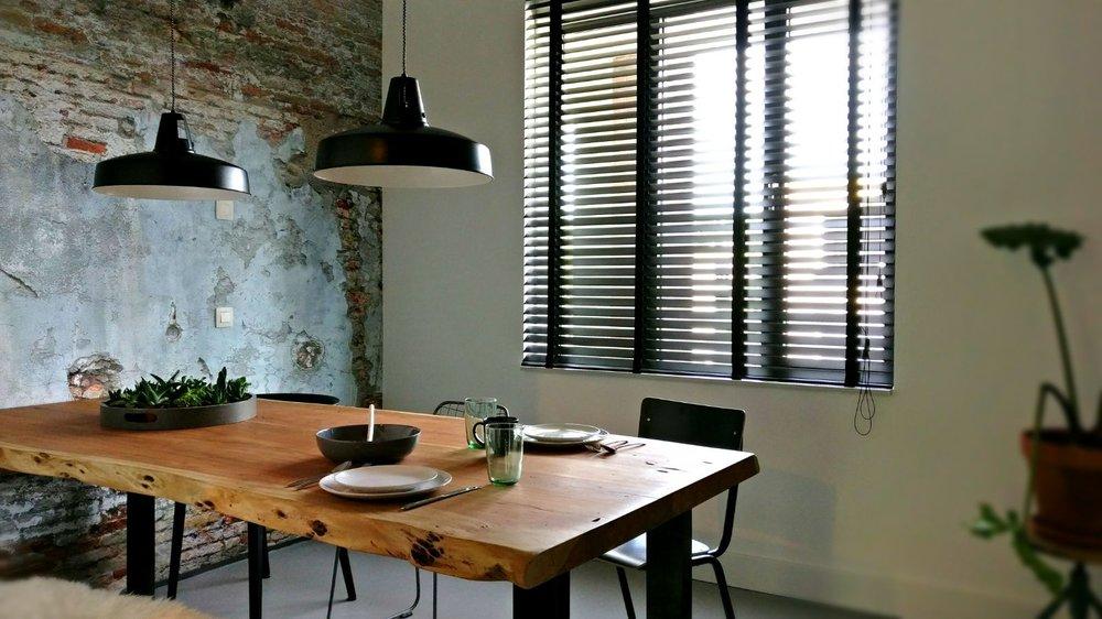 appartement nieuwbouw industrieel stoer boomstam tafel eettafel zwarte keuken eiken keuken planten urban jungle brick wall bakstenen muur.jpg
