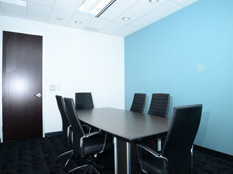 blue painted wall with a wooden black long table