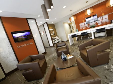 an orange wall with a brown leather sofa