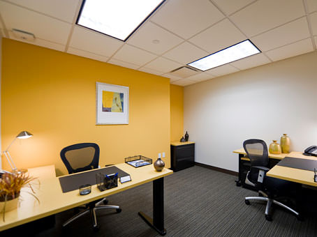 yellow wall and a painting with 2 tables