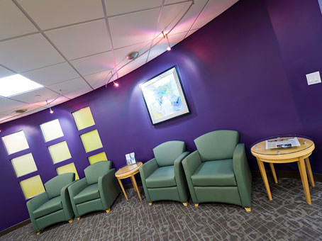 purple wall with a green leather sofa