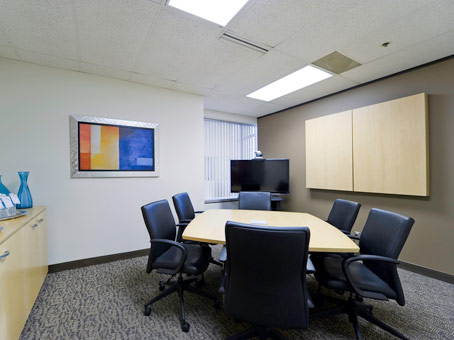 black chairs and round table with painting